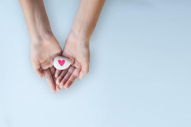 誰かに愛のハートのシンボルを与える女性の手広告の明るい背景テンプレート