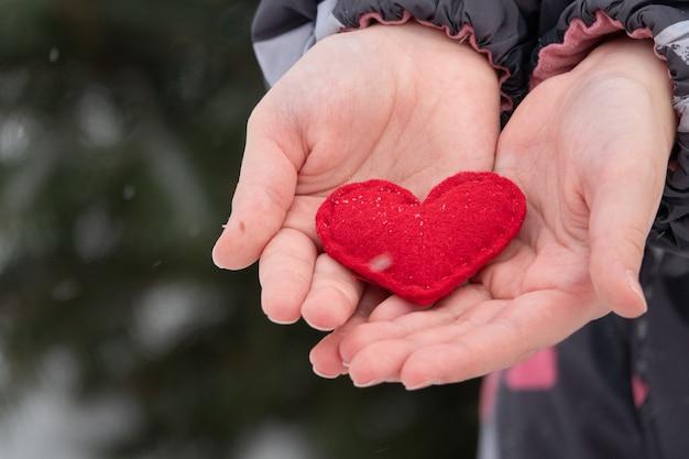 赤い手作りの心を屋外に与える女性の手