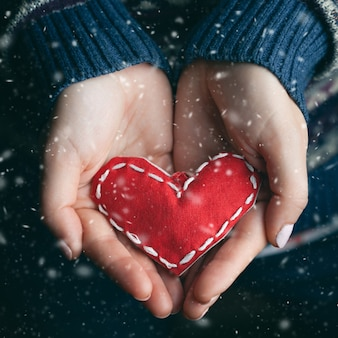 Женские руки, давая красное сердце крупным планом