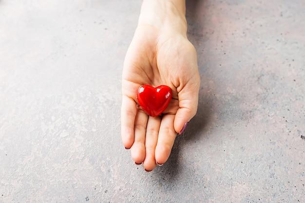 회색 배경 위에 붉은 마음을주는 여성 손