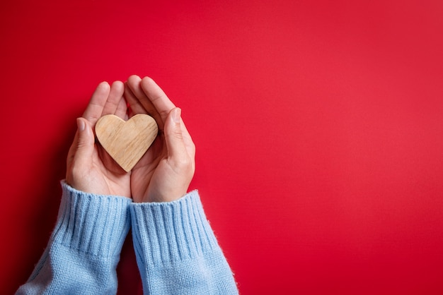 Female hands giving wood heart on red