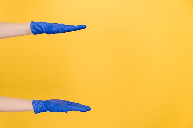 Female hands in gloves shows width of something pretends holding item