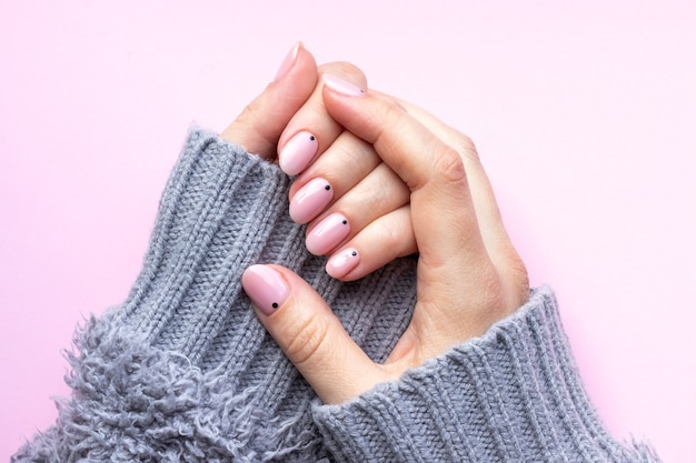 Female hands in a gray knitted sweater with trendy manicure