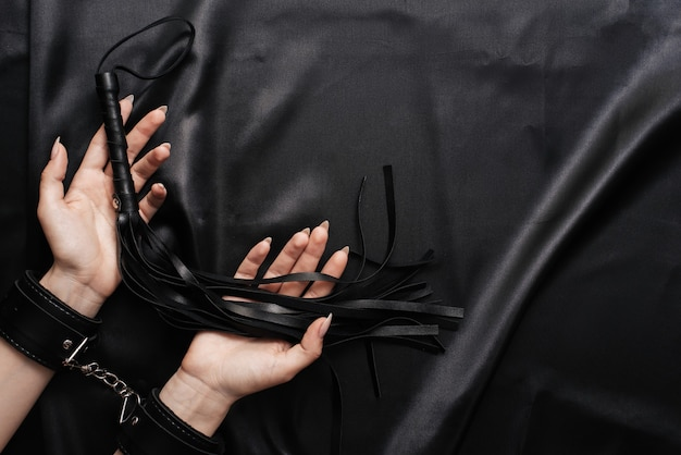 Female hands in handcuffs on a dark silk sheet with a whip