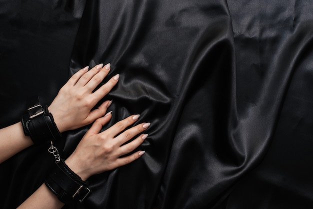 Female hands in handcuffs on a dark silk sheet