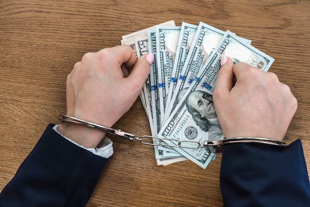 Female hands in handcuffs on dollar bribe