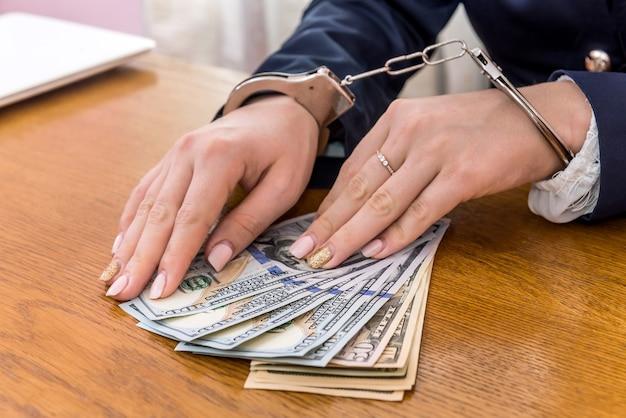 Female hands in handcuffs on dollar bribe