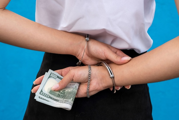 Female hands in handcuffs hold dollars isolated on blue.  prisoner or arrested