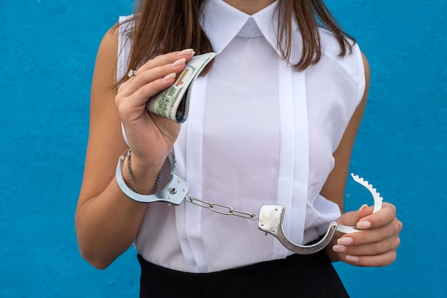 Female hands in handcuffs holds us money. concept of illegal business., corruption