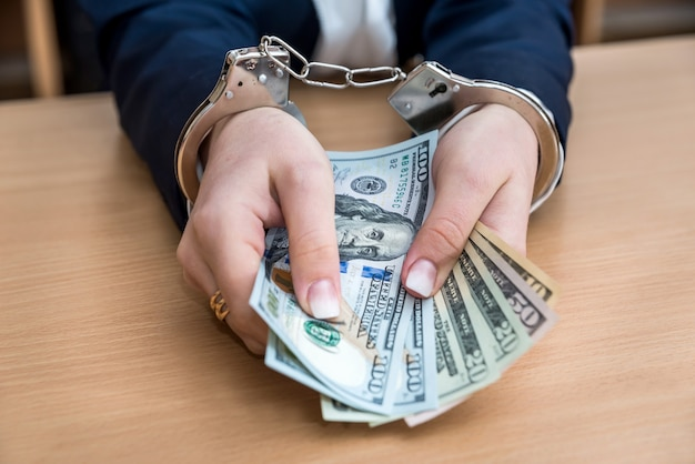 Female hands in handcuffs with dollar