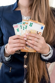 Female hands in handcuffs with euro notes
