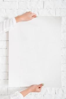 壁に空白のポスターをぶら下げ女性の手