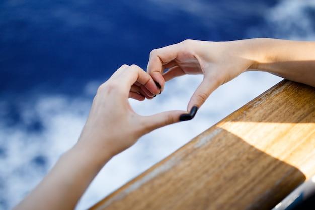 여성 손 나무 보드 후 들고 심장 모양. 자연 bokeh 햇빛 파와 푸른 파도 배경.