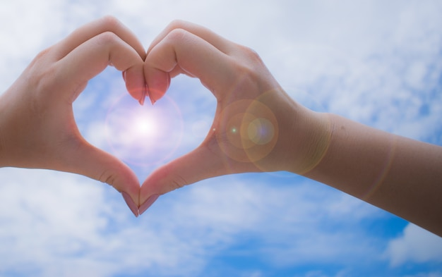 Female hands in heart shape with peaceful sky background.