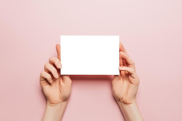 女性の手はピンクの背景に白紙を保持します。広告スペース