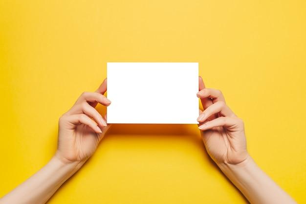 Женские руки держат чистый лист бумаги на желтом фоне