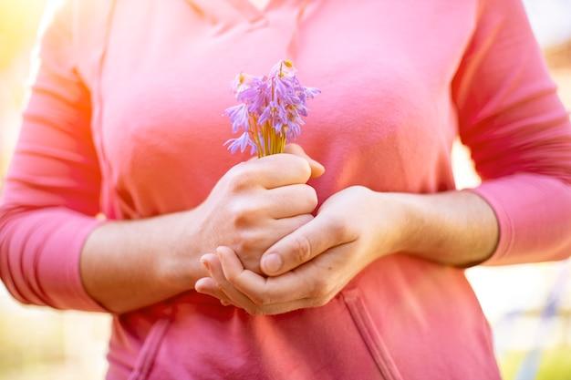 여성의 손은 얼굴이 없는 태양열에 파란색 스노드롭 꽃다발을 들고 있습니다.