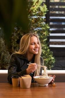 女性の手はアジアの伝統的なスープでボウルを保持します