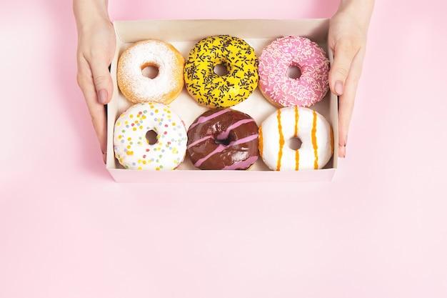 Женские руки держат коробку с глазированными пончиками на пастельно-розовом фоне. концепция кондитерского магазина, кондитерских изделий, кафе. вид сверху, плоская планировка, копия пространства