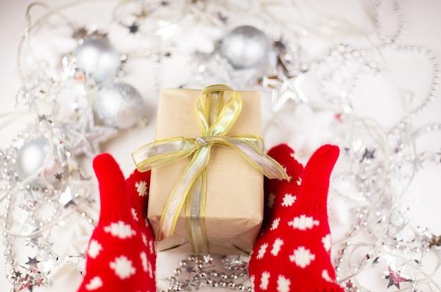 女性の手はクリスマスプレゼントを持っています