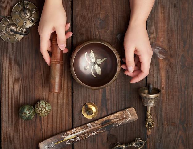 Женские руки держат медную тибетскую поющую чашу и деревянную палочку