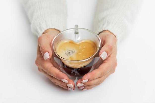 女性の手はハートの形をした一杯のコーヒーを持っています。上面図。