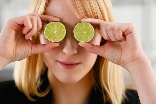 女性の手は、眼鏡の代わりに目の高さでカットフルーツを保持します