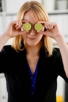 Женские руки держат разрезанный фрукт на уровне глаз