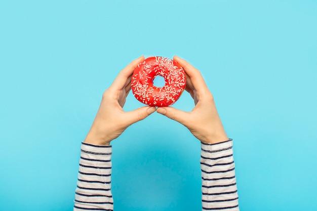 Женские руки держат пончик на синем. концепт кондитерский магазин, выпечка, кофейня.
