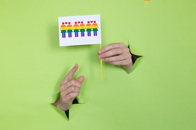 Женские руки держат флаг цветов радуги на зеленом фоне. концепция лгбт. место для рекламы.