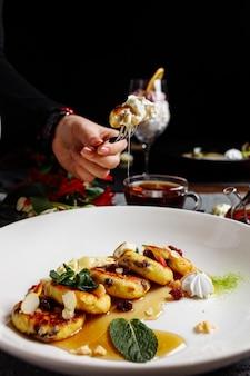 Женские руки держат вилку и нож с кусочками блинов. чизкейк, свежее варенье и мята. творожные оладьи или творожные оладьи украшали сахарную пудру в тарелке крупным планом.