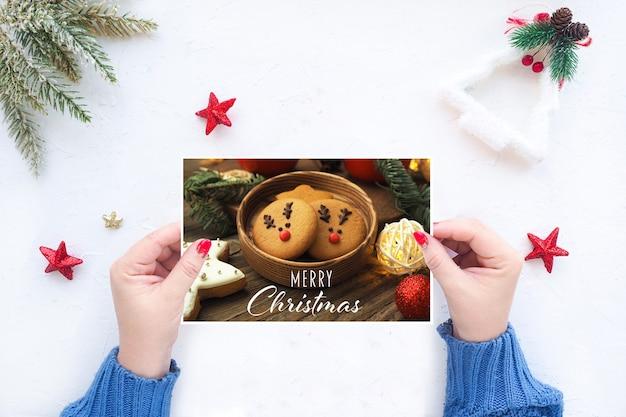 여성의 손은 크리스마스 장식이 있는 흰색 테이블 배경에 크리스마스 인사말 카드를 들고 있습니다.