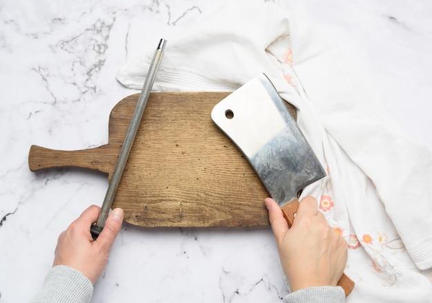 여성의 손을 잡고 부엌 칼과 손잡이가 달린 숫돌