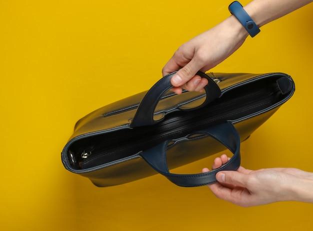 여성의 손에 노란색 배경에 핸들로 가죽 가방을 잡으십시오. 평면도