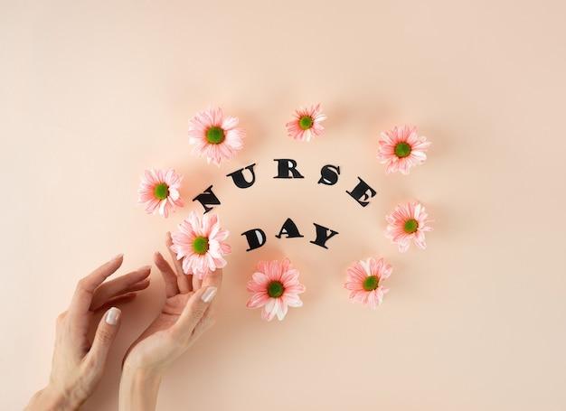 女性の手は白い医療マスクとパステルピンクの背景にピンクの菊を保持します。
