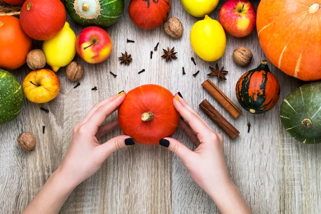 秋の背景に女性の手がカボチャを持っています。木製の背景にカボチャと果物から秋の背景。