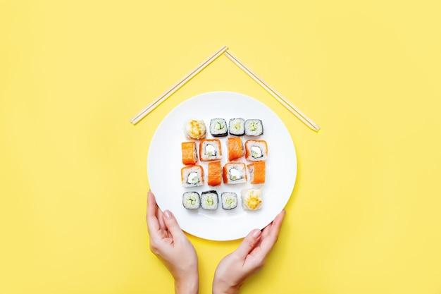 女性の手は使い捨ての背景にロールパンと寿司の白い皿を持っています。宅配の概念。スパイスに対処する