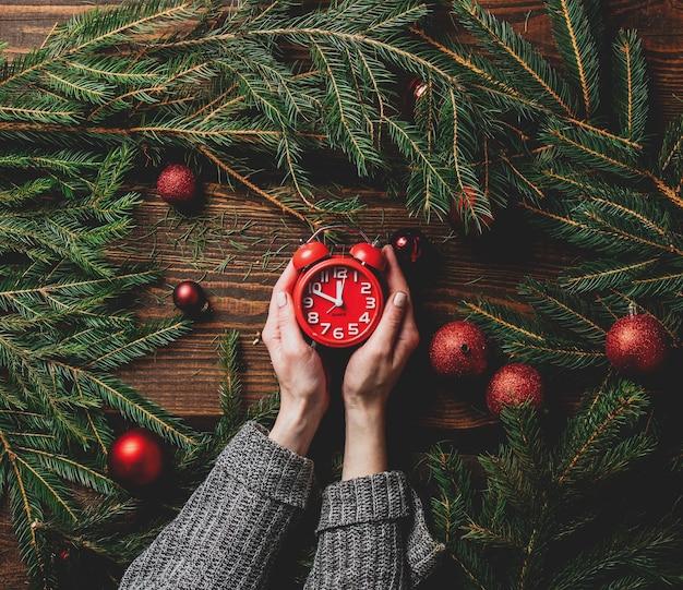 女性の手はクリスマスの装飾の横に目覚まし時計を保持します