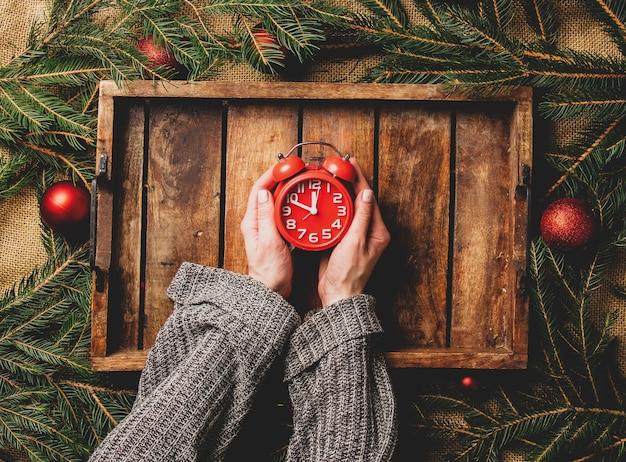 女性の手はクリスマスの装飾の横にあるトレイの上に目覚まし時計を保持します