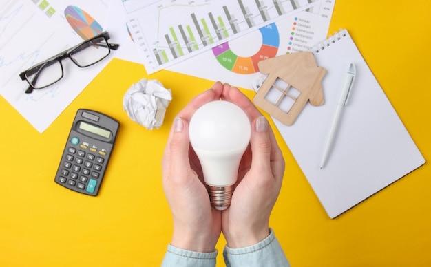 女性の手は、グラフ、チャート、電卓を備えた黄色の省エネ電球を持っています