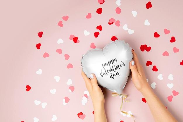 Женские руки держат воздушный шар фольги в форме сердца на пастельно-розовом фоне. концепция любви. праздник. день святого валентина или украшение свадьбы / девичника. металлический шар