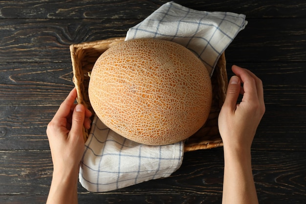 Female hands hold basket with melon on wooden table