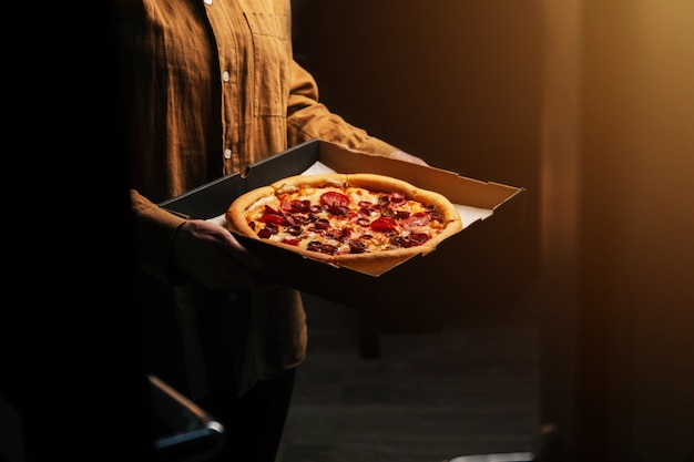 Female hands hold a beautiful tasty pepperoni pizza in front of the door