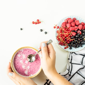 Female hands hold a berry smoothie in a bowl next to a plate with raspberries