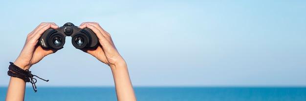 여성의 손은 하늘과 바다를 배경으로 쌍안경을 들고 있습니다. 배너.