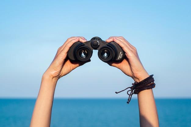 여성의 손은 하늘과 바다를 배경으로 쌍안경을 들고 있습니다.