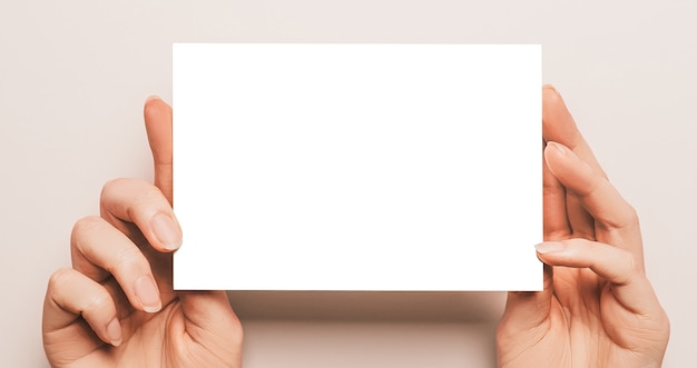 Female hands hold a blank sheet of paper on a beige wall