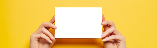 Female hands hold a blank sheet of paper on a yellow background. advertising space