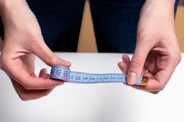 Female hands hold blue tape measure