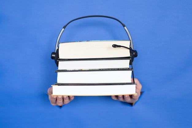 Женские руки держат книги и наушники на синем фоне. женские вставлены в бумажный фон. место для надписи.